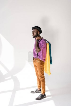 young african american man in fashionable clothing and hat holding hangers with colorful textile on grey background