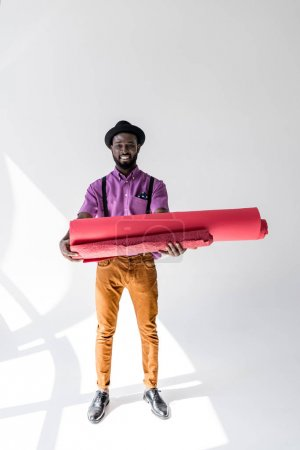 smiling african american in hat holding pink wrapping paper rolls in hands on grey backdrop