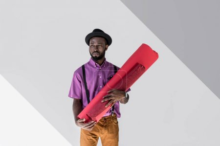 pensive fashionable african american in hat holding pink wrapping paper rolls in hands on grey backdrop