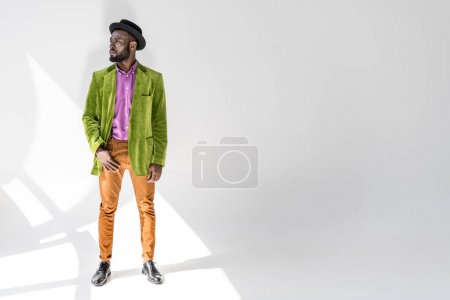 thoughtful african american man in fashionable clothing and hat posing on grey backdrop
