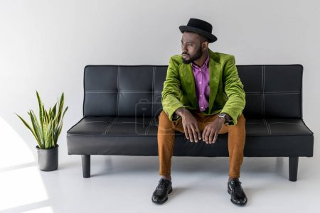 pensive african american fashionable man in hat sitting on black sofa