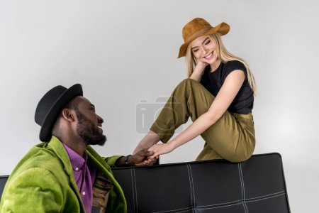 smiling multicultural fashionable couple in hats holding hands on black sofa isolated on grey