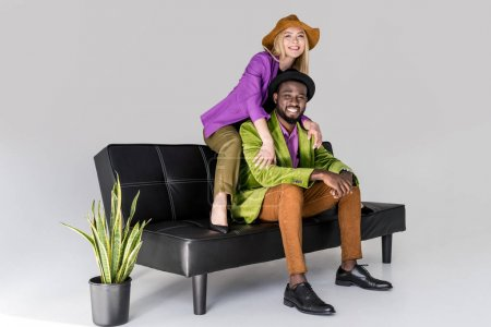 cheerful multicultural fashionable couple in hats sitting on black sofa on grey background