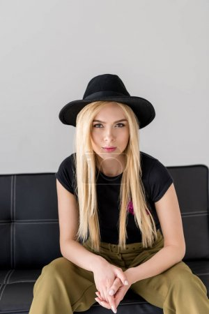 portrait of attractive woman in black hat looking at camera while sitting on sofa isolated on grey