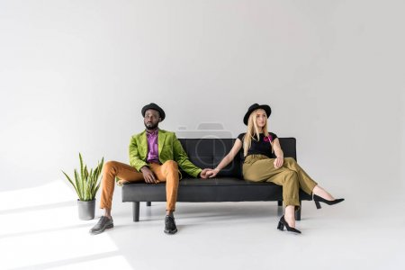 Photo for Stylish young multiethnic couple holding hands while sitting on sofa and looking away on grey - Royalty Free Image