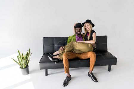happy young multiethnic couple in stylish clothes sitting on sofa and smiling at camera on grey