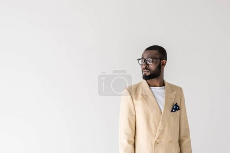 portrait of handsome young stylish african american man in eyeglasses looking away isolated on grey
