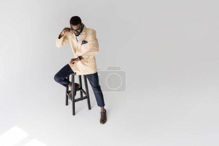 Photo pour Vue grand angle de la mode homme afro-américain assis sur le tabouret et la vérification montre-bracelet isolé sur fond gris - image libre de droit