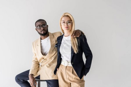 portrait of stylish young multiethnic couple in eyeglasses looking at camera isolated on grey