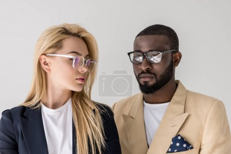 portrait of beautiful stylish young multiethnic couple in eyeglasses isolated on grey