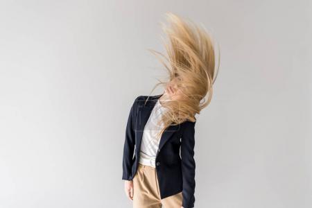 beautiful stylish blonde girl shaking hair isolated on grey