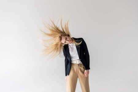beautiful young blonde woman shaking hair isolated on grey