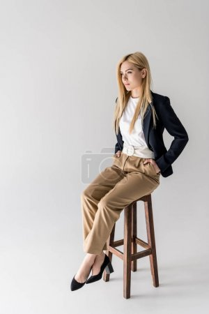 full length view of beautiful stylish blonde girl sitting on chair and looking away isolated on grey