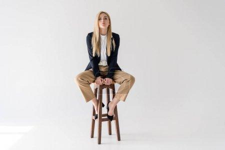 schöne junge blonde Frau in stilvoller Kleidung sitzt auf einem Schemel und schaut in die Kamera isoliert auf grau