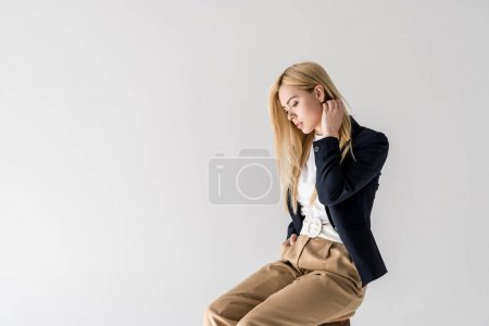 Photo for Portrait of beautiful young blonde woman in fashionable clothes sitting and looking down isolated on grey - Royalty Free Image