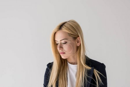 portrait of beautiful young blonde woman looking down isolated on grey
