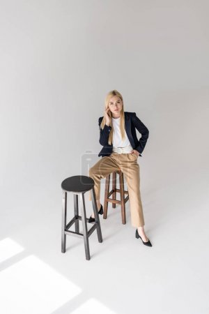 Photo for High angle view of beautiful stylish blonde girl sitting on stool and looking at camera on grey - Royalty Free Image