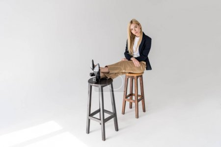 beautiful stylish young woman sitting on stools and looking at camera on grey