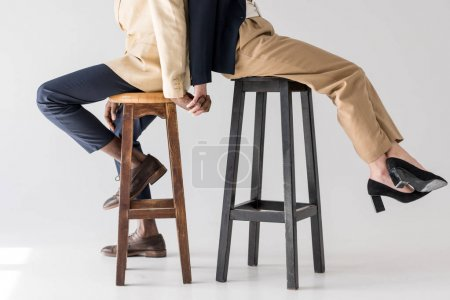 cropped shot of multiethnic couple sitting back to back on stools and holding hands on grey
