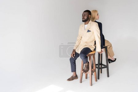 high angle view of fashionable young multiethnic couple sitting back to back on grey