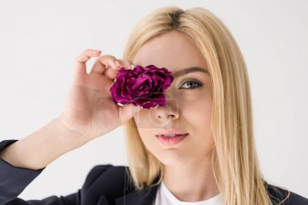 close-up view of beautiful blonde girl holding flower and looking at camera