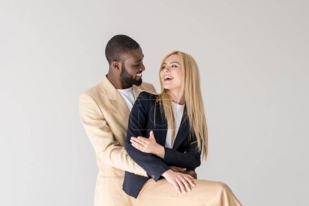 Photo for Happy stylish young multiethnic couple hugging and smiling each other isolated on grey - Royalty Free Image