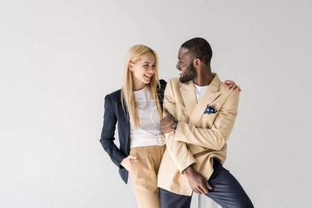 happy young stylish multiethnic couple smiling each other isolated on grey
