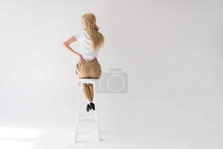 Photo pour Vue arrière de la fille blonde assise sur un tabouret et touchant les cheveux sur du gris - image libre de droit