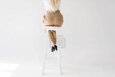 Photo pour Plan recadré de fille blonde assise sur un tabouret sur du gris - image libre de droit