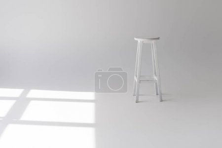 Photo for Single empty modern white stool on grey - Royalty Free Image