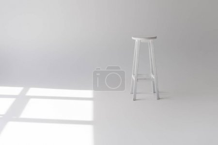 single empty modern white stool on grey