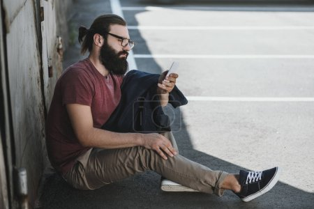 man sitting on floor and using phone