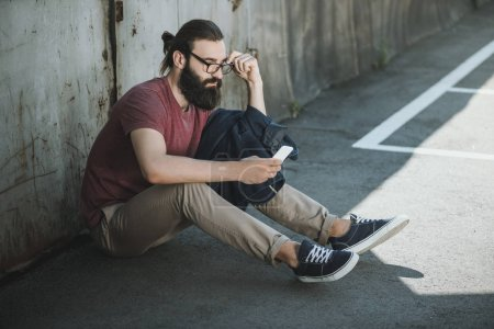 Photo for Handsome man sitting on floor and using phone outdoors - Royalty Free Image