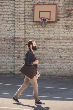 Photo for Handsome man passing through basketball yard - Royalty Free Image