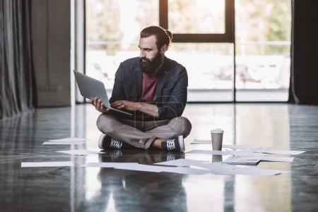 Photo pour Bel homme d'affaires barbu avec ordinateur portable et paperasse assis sur le sol - image libre de droit