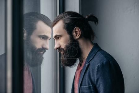 Thoughtful bearded man looking at reflection in gl...