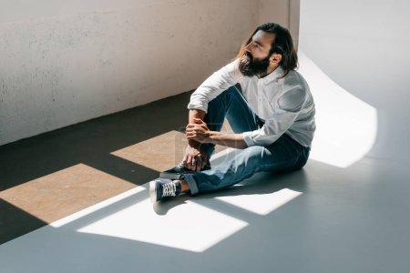 handsome man sitting on floor