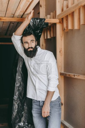 Photo for Handsome relaxed bearded man posing in wooden construction - Royalty Free Image