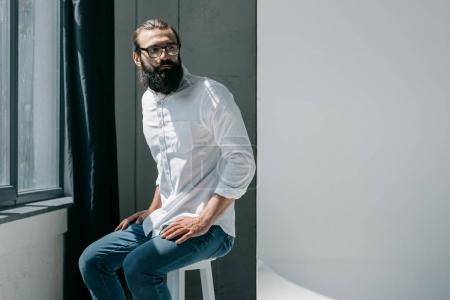 Photo for Handsome bearded man sitting on chair and looking away - Royalty Free Image