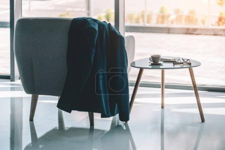 Businessmans jacket hanging on armchair