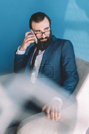 bearded businessman talking by phone