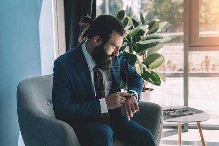 Handsome businessman looking at watch