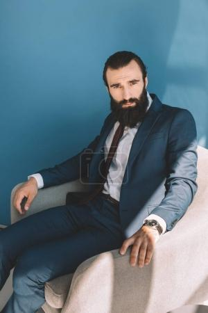 bearded businessman sitting in armchair