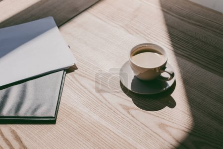 Cup of coffee and notebooks on table