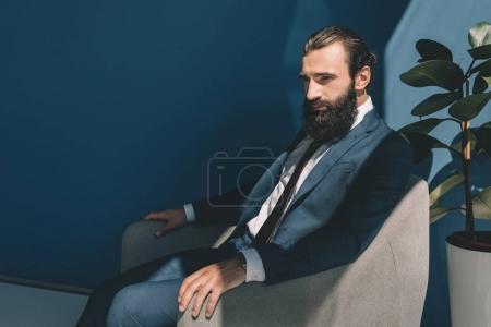 Photo pour Bel homme d'affaires barbu assis dans un fauteuil - image libre de droit