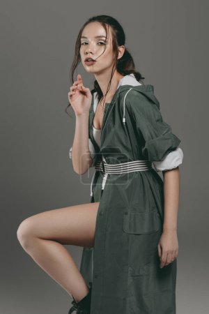 young elegant girl posing in autumn outfit, isolated on grey