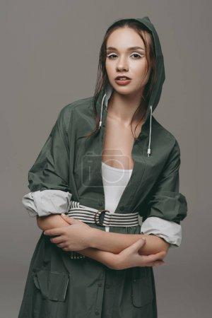 beautiful young girl posing in raincoat, isolated on grey