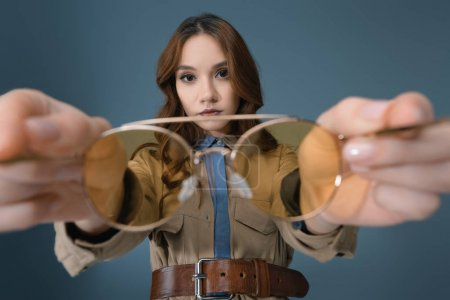 Photo for Attractive girl holding yellow sunglasses, isolated on grey - Royalty Free Image