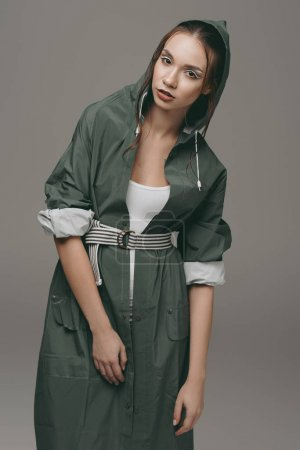 stylish girl posing in green autumn raincoat, isolated on grey