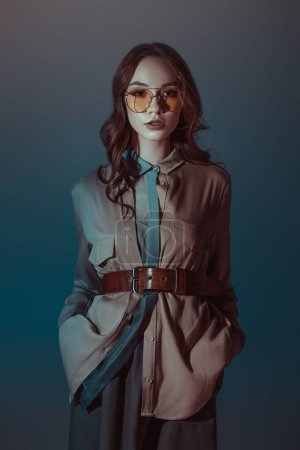 trendy girl posing in autumn outfit and sunglasses, isolated on grey